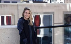 University of Minnesota alum Elise Eckert poses for a portrait on a balcony in downtown Minneapolis on Tuesday, March 30. Eckert, who graduated in Spring 2020, filed independently on her 2020 taxes for the first time, prompted by the opportunity to receive a stimulus check.