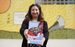 Jamie Schumacher poses for a portrait outside of Keefer court in Cedar Riverside with her new book on Tuesday, April 27. The book will be released on May 18 and details different stories and conversations with local business owners, residents and creatives who make the West Bank and Cedar-Riverside neighborhood a special place.