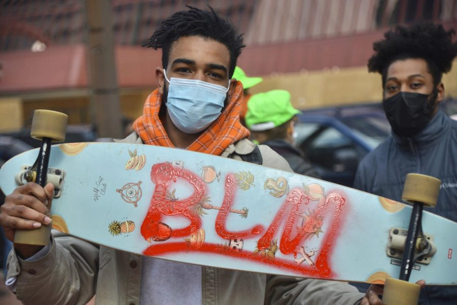 A skateboarder poses for a portrait on Tuesday, April 20, with his skateboard adorned with
