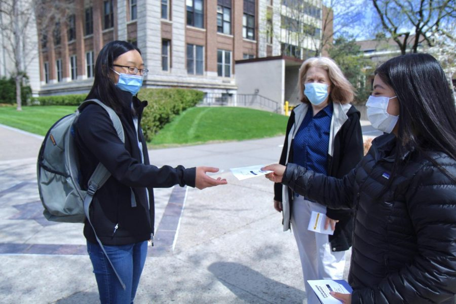 12:50 p.m. A student group member hands a pamphlet to another student on the Northrop Mall.
