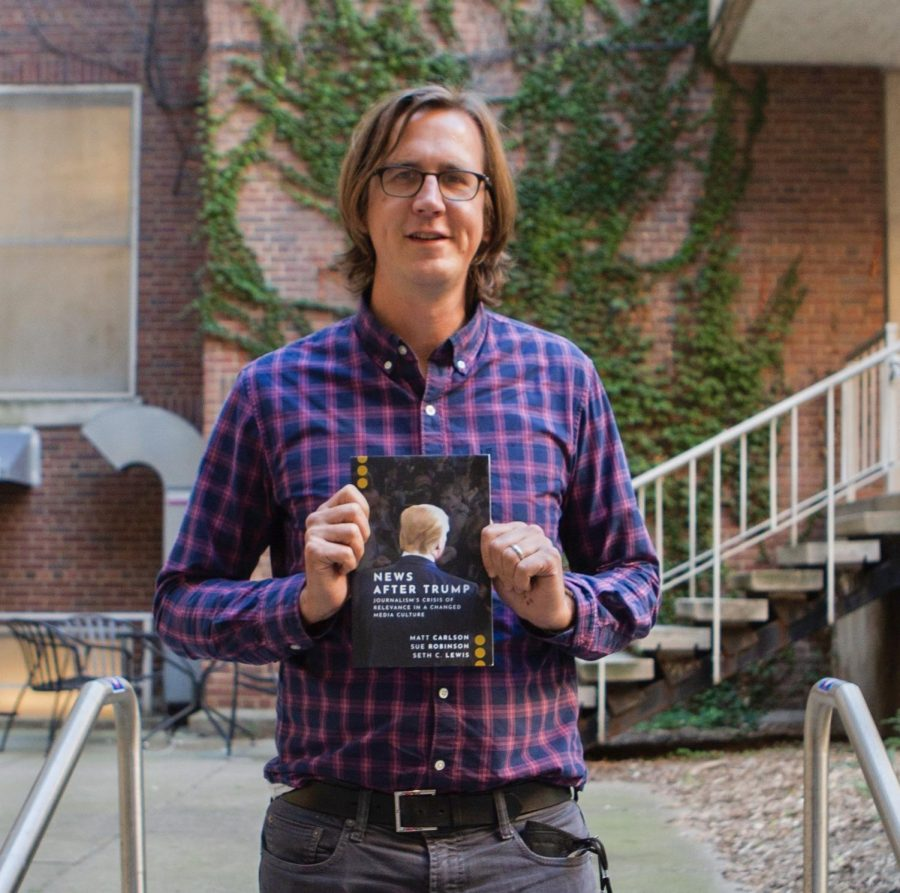 UMN Professor Matt Carlson poses for a portrait with his new book, New After Trump, on Tuesday, Oct. 26.